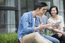 Chinese casual business team talking with digital tablet in city — Stock Photo