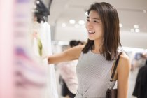 Chinese woman shopping in clothing store — Stock Photo