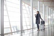 Donna asiatica in piedi con i bagagli nella hall dell'aeroporto — Foto stock