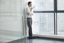 Chinese businessman thinking and looking through window in office — Stock Photo