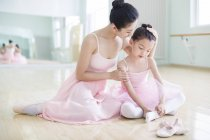 Chinese ballet instructor and tired girl sitting in ballet studio — Stock Photo