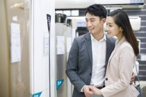 Chinese couple buying air conditioner in electronics store — Stock Photo