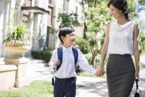 Mère chinoise marchant main dans la main avec un écolier — Photo de stock