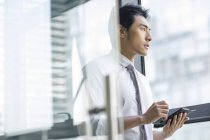 Chinese businessman using smartphone in office and looking through window — Stock Photo