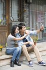 Chinese couple taking selfie with smartphone on street — Stock Photo