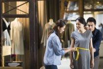Chinese fashion designers taking measurement of customer — Stock Photo