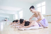 Chinese ballet instructor teaching girls in ballet studio — Stock Photo