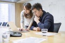 Китайские офисные работники используют ноутбук в бортовой комнате — стоковое фото