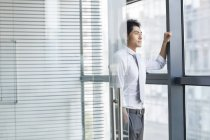 Chinese businessman leaning on doorway and looking through window — Stock Photo