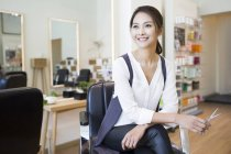 Female chinese barber sitting in shop — Stock Photo