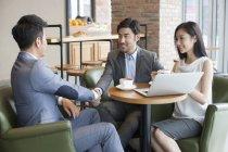 Азиатский бизнес пожимает руку во время встречи в кафе — стоковое фото