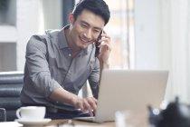 Asian man talking on phone in office — Stock Photo