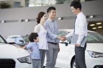 Китайская семья, пожимая руки с продавцом автомобилей в салоне — стоковое фото