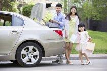 Familia china tomando bolsas de compras del maletero del coche - foto de stock