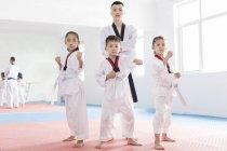 Chinese instructor posing in exercise room with Taekwondo students — Stock Photo