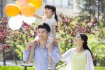 Щасливий китайський сім'ї прогулянка у парку з повітряними кульками — стокове фото
