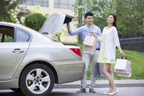 Chino pareja tomando bolsas de compras de coche tronco - foto de stock