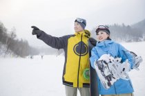 Chinese couple of snowboarders standing on slope — Stock Photo