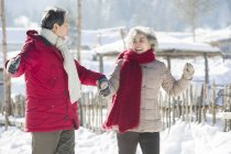 Chinese senior couple holding hands while walking outdoors — Stock Photo