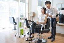 Chinese hairdresser working on customer — Stock Photo