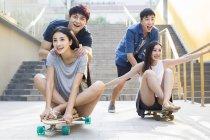 Chinesische Männer schieben Freundinnen auf skateboards — Stockfoto