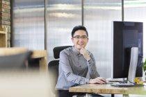 Chinesischen Büroangestellten im Büro sitzen — Stockfoto
