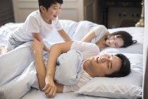 Chinesischer Junge weckt Eltern im Schlafzimmer — Stockfoto