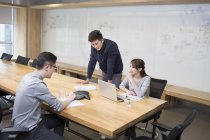 Chinese office workers having teleconference in board room — Stock Photo