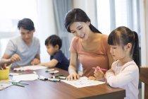 Chinois frères et sœurs dessin avec les parents à la maison — Photo de stock
