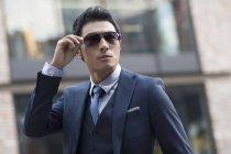 Uomo asiatico mettendo su occhiali da sole sulla via urbana — Foto stock