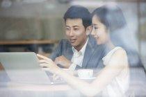 Asiatischer Mann und Frau arbeiten mit Laptop im café — Stockfoto