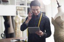 Designer de moda asiática falando no telefone em estúdio e segurando tablet digital — Fotografia de Stock