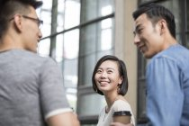 Chinese friends talking in city with coffee — Stock Photo