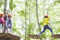 Chinese children climbing on trees in adventure park — Stock Photo