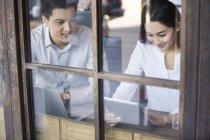 Homem e mulher chineses usando tablet digital no café — Fotografia de Stock