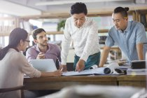 Architects discussing blueprints in office — Stock Photo