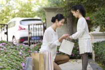 Chinese mother and daughter looking into shopping bag — Stock Photo