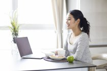 Asian woman using laptop while having breakfast — Stock Photo