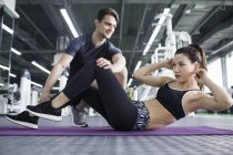 Asian woman working with trainer at gym — Stock Photo