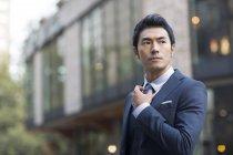 Asian man straightening tie on street — Stock Photo