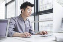Chinesischer Geschäftsmann mit Computer im Büro — Stockfoto