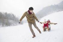 Китайський батько потягнувши дітей на салазках — стокове фото