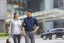 Mature chinese couple walking in city — Stock Photo
