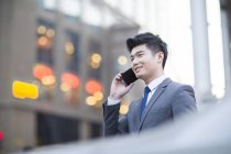 Chinese businessman talking on phone on street — Stock Photo