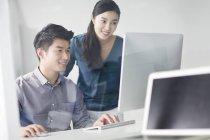 Китайськими колегами за допомогою комп'ютера в офісі — стокове фото