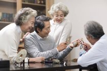 Senior Chinese friends admiring antiques — Stock Photo
