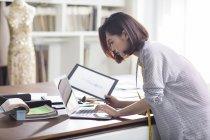 Женский модный дизайнер работает в студии с ноутбуком — стоковое фото