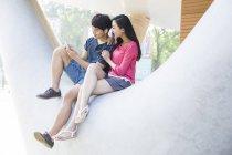 Китайская пара, слушать музыку на смартфон на улице — стоковое фото
