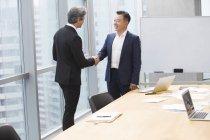 Бизнесмены, пожимая руки в Конференц-зал — стоковое фото