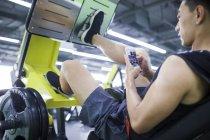 Asian man using phone on exercise machine — Stock Photo